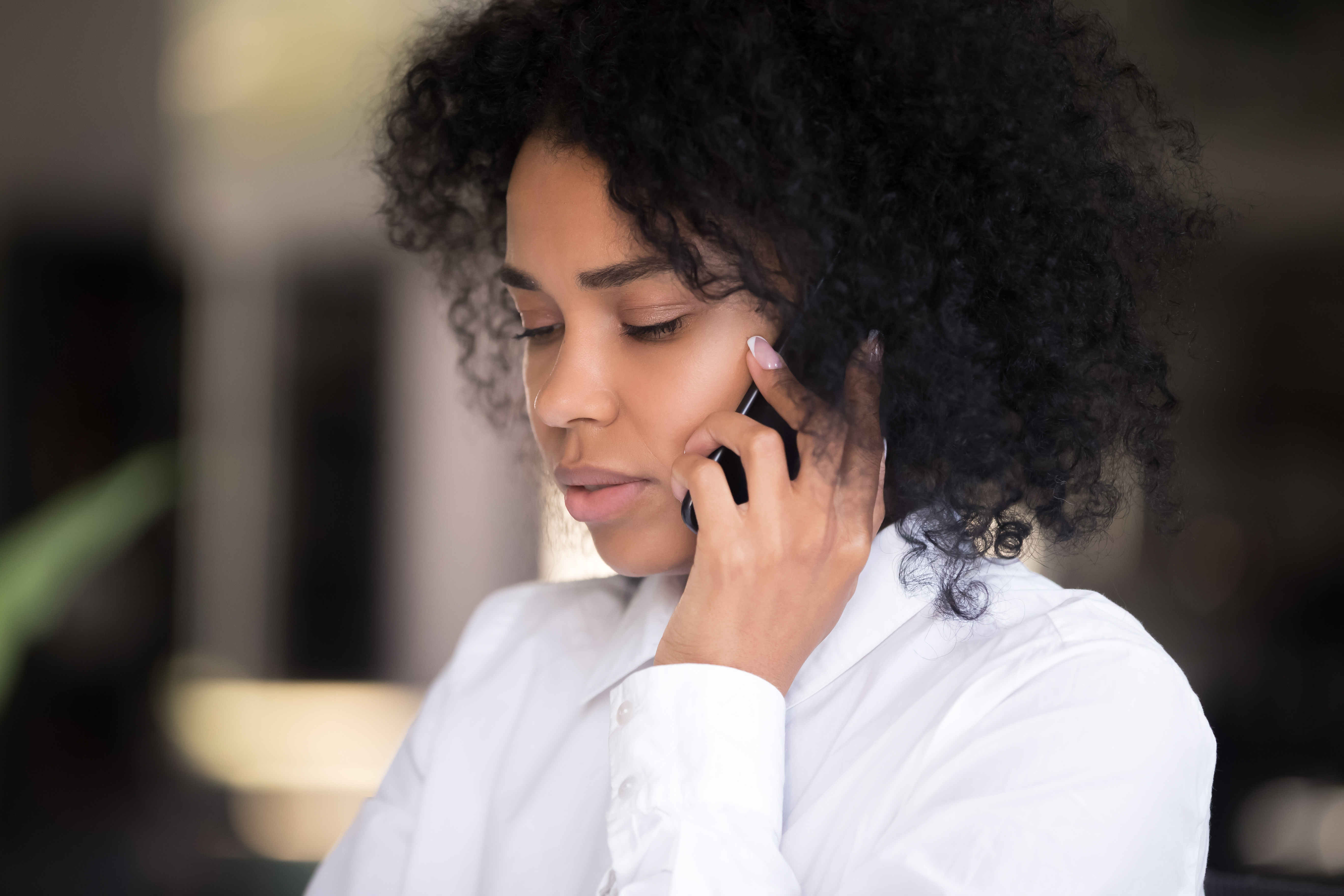 Close up of pensive millennial African American woman talk on smartphone thinking of idea or news, serious black female speak over cell, lost in thoughts considering something. Technology concept